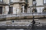FILE - In this Dec. 2, 20118 file photo, a man rides his bicycle past by a graffiti on the Paris Garnier Opera house in Paris that reads: