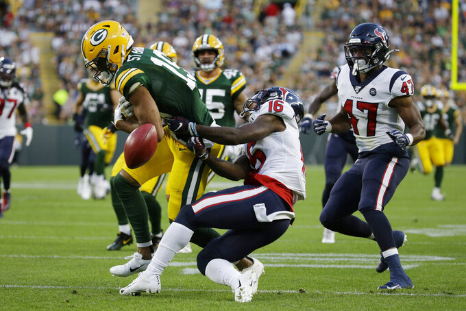 Green Bay Packers' Equanimeous St. Brown knocks a muffed punt out of the hands of Houston Texans' Keke Coutee during the first half of an NFL preseason football game Thursday, Aug. 8, 2019, in Green Bay, Wis. St. Brown recovered the ball for a touchdown. (AP Photo/Mike Roemer)