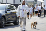 Mercedes driver Lewis Hamilton of Britain and his dog Roscoe arrive at the Monza racetrack, in Monza, Italy, Thursday, Sept. 9, 2021. The Italian Formula One Grand Prix will be held on Sunday. (AP Photo/Luca Bruno)