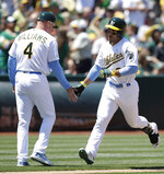 Oakland Athletics' Ramon Laureano, right, is congratulated by third base coach Matt Williams (4) after hitting a home run off Seattle Mariners' Mike Leake in the fourth inning of a baseball game Sunday, June 16, 2019, in Oakland, Calif. (AP Photo/Ben Margot)