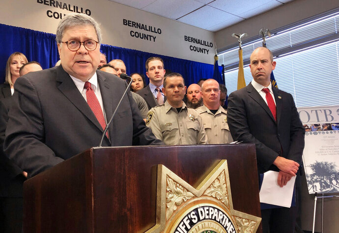 U.S. Attorney General William Barr, left, with other federal and officials, announces that nearly 330 fugitives suspected of violent crimes have been arrested as part of a crime-fighting initiative in New Mexico, at a news conference at the office of the Bernalillo County Sheriff in Albuquerque Tuesday, Nov. 12, 2019. Barr was in Albuquerque to highlight the results of Operation Triple Beam, a program that has been conducted in numerous U.S. cities and has led to hundreds of arrests. (AP Photo/Mary Hudetz)
