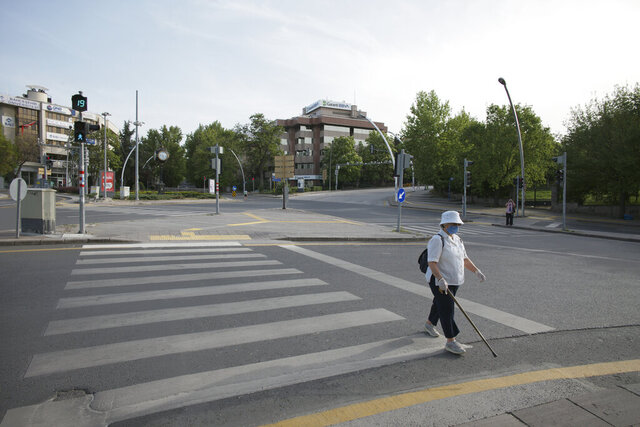 Sevim Kocak, 79, wearing a face mask for protection against coronavirus, walks along the city's main Ataturk Boulevard during a four-day curfew declared by the government in an attempt to control the spread of coronavirus, in Ankara, Turkey, Sunday, May 17, 2020. Turkey's senior citizens were allowed to leave their homes for a second time as the country continues to ease some coronavirus restrictions. (AP Photo/Burhan Ozbilici)