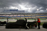 A pit crew covers a truck during a weather delay at a NASCAR Truck Series race Saturday, July 11, 2020, in Sparta, Ky. (AP Photo/Mark Humphrey)