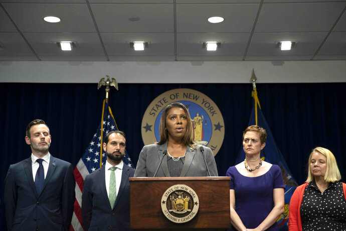 New York Attorney General Letitia James, center, speaks during a news conference, Tuesday, June 11, 2019, in New York. A group of state attorneys general led by New York and California filed a federal lawsuit Tuesday to block T-Mobile's $26.5 billion bid for Sprint, citing consumer harm. (AP Photo/Mary Altaffer)
