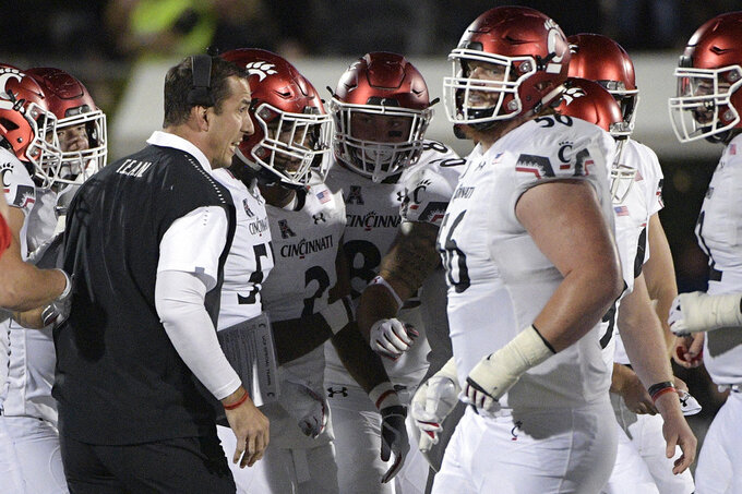 Cincinnati head coach Luke Fickell, left, gives instructions to his players on the sideline during the first half of an NCAA college football game against Central Florida Saturday, Nov. 17, 2018, in Orlando, Fla. (AP Photo/Phelan M. Ebenhack)