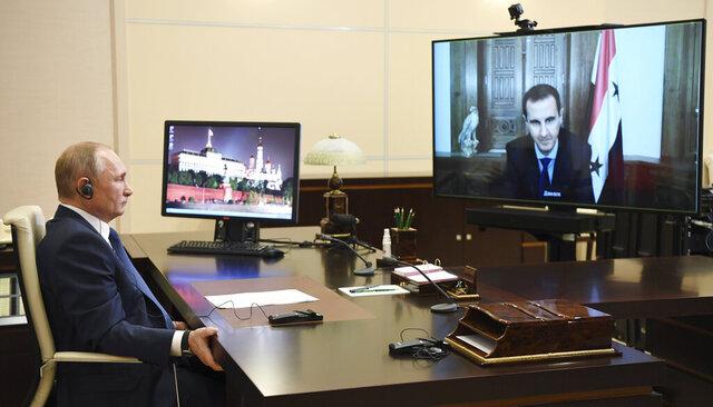 Russian President Vladimir Putin, listens to Syrian President Bashar Assad, right on screen, during their talks via video conference at the Novo-Ogaryovo residence outside Moscow, Russia, Monday, Nov. 9, 2020. (Alexei Nikolsky, Sputnik, Kremlin Pool Photo via AP)