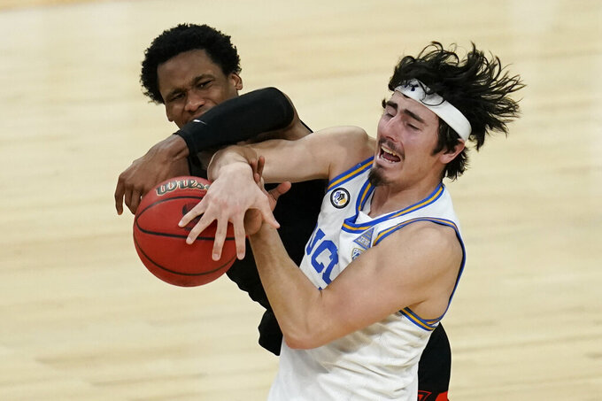 Oregon State's Gianni Hunt, left, fouls UCLA's Jaime Jaquez Jr. during the second half of an NCAA college basketball game in the quarterfinal round of the Pac-12 men's tournament Thursday, March 11, 2021, in Las Vegas. (AP Photo/John Locher)
