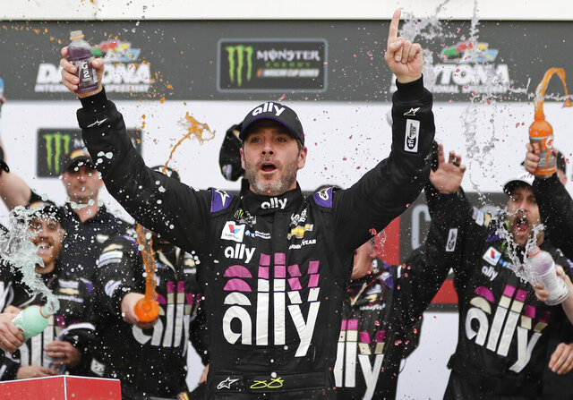 FILE - In this Feb. 10, 2020, file photo, Jimmie Johnson celebrates in Victory Lane after winning the NASCAR Clash auto race at Daytona International Speedway in Daytona Beach, Fla. Seven-time NASCAR champion Jimmie Johnson has twice tested negative for the coronavirus and has been cleared to race Sunday, July 12, 2020 at Kentucky Speedway. Johnson missed the first race of his Cup career when he tested positive last Friday. (AP Photo/John Raoux, File)