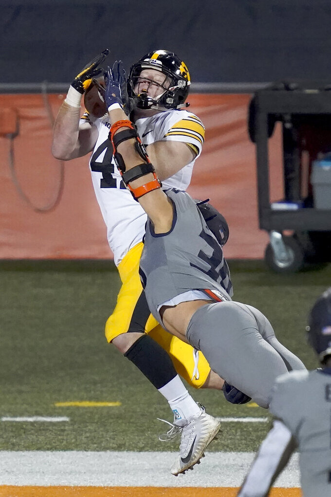 Iowa tight end Shaun Beyer catches a touchdown pass as Illinois defensive back Sydney Brown defends during the second half of an NCAA college football game Saturday, Dec. 5, 2020, in Champaign, Ill. (AP Photo/Charles Rex Arbogast)