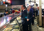 Democratic presidential candidate Michael Bloomberg, center, joins Los Angeles Mayor Eric Garcetti at Philippe The Original, a historic deli serving up signature French dip sandwiches in downtown Los Angeles on Monday, Jan. 6, 2020. The Democratic presidential candidate and former New York City mayor likes a lot of what he sees in the Golden State and thinks its efforts on climate change, gun control and criminal justice reform sets a benchmark for other states to emulate. (AP Photo/Michael R. Blood)