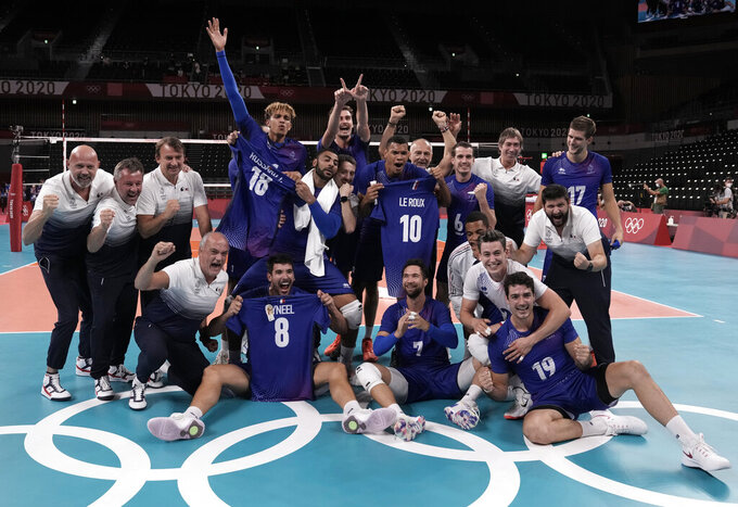 Team France poses for a group photo after winning the men's volleyball gold medal match against the Russian Olympic Committee, at the 2020 Summer Olympics, Saturday, Aug. 7, 2021, in Tokyo, Japan. (AP Photo/Manu Fernandez)