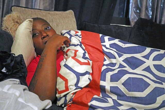 In this Dec. 18, 2019 photo,  Crystal Roberts curls up on a friends sofa after being evicted from her subsidized apartment at Fort Myers, Fla., Southward Village earlier in the day,  a week before Christmas. Roberts, who is disabled and suffers chronic bronchitis, is one of a growing number who residents allege the City of Fort Myers Housing Authority has evicted in order to avoid giving them vouchers as it is required to do when it tears down the aging complex and replaces it with new, mixed income housing. (Andrew West/The News-Press via AP)