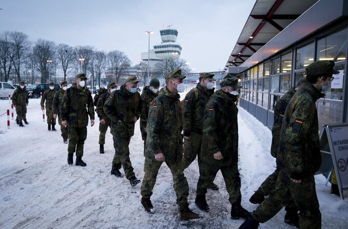 Bundeswehr soldiers wearing mouth-nose coverings go to the fourth vaccination centre in Berlin, located in Terminal C of the former Tegel Airport, Germany, Wednesday, Feb.10, 2021.  Here, at the beginning, mainly nursing staff and medical personnel are vaccinated against the coronavirus. (Kay Nietfeld/Pool via AP)