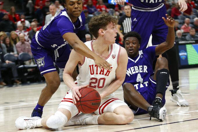 Weber State guard Judah Jordan, left, defends against Utah forward Mikael Jantunen (20) in the second half during an NCAA college basketball game Saturday, Dec. 14, 2019, in Salt Lake City. (AP Photo/Rick Bowmer)