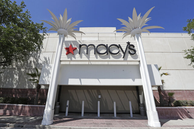 FILE - In this March 30, 2020 file photo, the entrance to a Macy's department store is closed behind barriers and storm shutters remains closed  in Orlando, Fla. Macy's said Thursday, June 25, it's laying off 3,900 corporate staffers, roughly 3% of its overall workforce, as the pandemic takes a financial toll on the retailer's business.  (AP Photo/John Raoux, File)