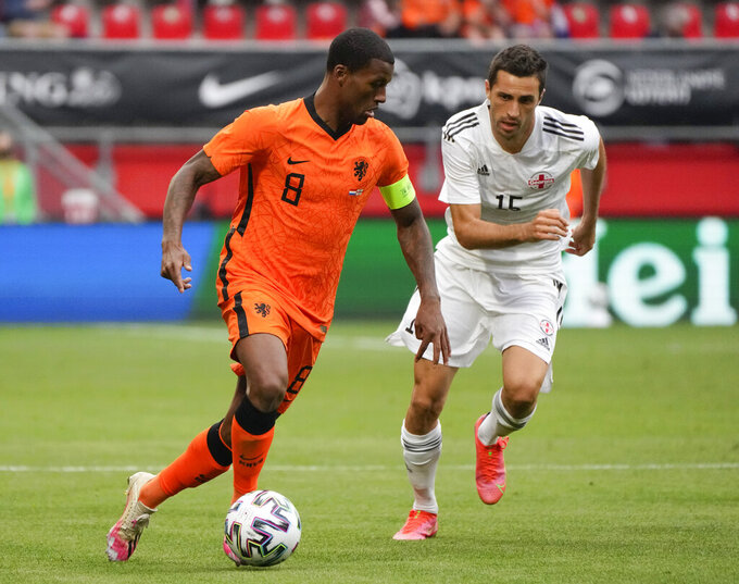 Netherlands' Georginio Wijnaldum, left, and Georgia's Giorgi Aburjania vie for the ball during the friendly soccer match between The Netherlands and Georgia, in the run-up to the Euro2020 soccer tournament, in Enschede, eastern Netherlands, Sunday, June 6, 2021. (AP Photo/Peter Dejong)