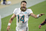 Miami Dolphins quarterback Ryan Fitzpatrick laughs with coaches as he comes off the field after defeating the Jacksonville Jaguars in an NFL football game, Thursday, Sept. 24, 2020, in Jacksonville, Fla. (AP Photo/Phelan M. Ebenhack)