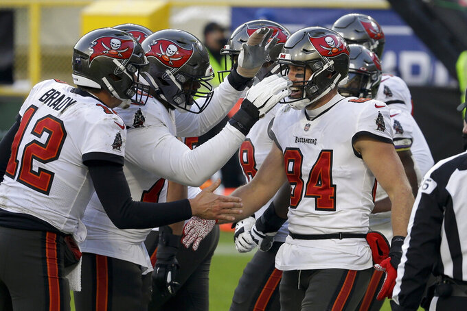 Tampa Bay Buccaneers' Cameron Brate (84) is congratulated after scoring on an 8-yard touchdown pass against the Green Bay Packers during the second half of the NFC championship NFL football game in Green Bay, Wis., Sunday, Jan. 24, 2021. (AP Photo/Mike Roemer)