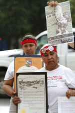 Raynadia Thomas, left, and Diane Uriegas hold county and city proclamations during a news conference by members of the Native American community in front of the U.S. Postal Service building across the Alamo, Monday, Oct. 14, 2019 in San Antonio. A Native American group is calling on officials to slow down the renovation of the Alamo church in San Antonio, after archaeological reports showed human remains were found at the property. (Jerry Lara/The San Antonio Express-News via AP)