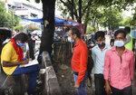 A health worker registers people for the COVID-19 test near a metro station, in New Delhi, India, Tuesday, July 13, 2021. (AP Photo/Manish Swarup)