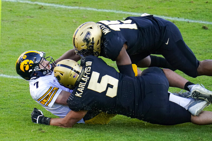 Iowa quarterback Spencer Petras (7) is sacked by Purdue defensive end George Karlaftis (5) and linebacker DaMarcus Mitchell (15) during the second quarter of an NCAA college football game in West Lafayette, Ind., Saturday, Oct. 24, 2020. (AP Photo/Michael Conroy)
