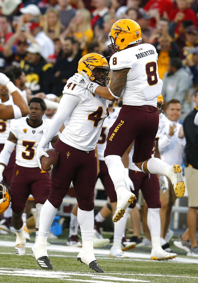 Arizona State defensive lineman Tyler Johnson (41) celebrates with Arizona State linebacker Merlin Robertson (8) after recovering a fumble in the second half during an NCAA college football game against Arizona, Saturday, Nov. 24, 2018, in Tucson, Ariz. (AP Photo/Rick Scuteri)