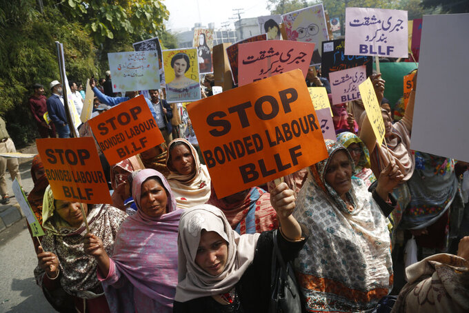 FILE - In this March 8, 2020 file photo, Pakistani activists take part in an International Women's Day rally in Lahore, Pakistan.  A new report on Friday, Oct. 9, 2020,  estimates that 29 million women and girls are victims of modern slavery, exploited by practices including forced labor, forced marriage, debt-bondage and domestic servitude.  (AP Photo/K.M. Chaudhry)
