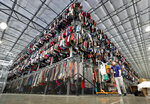 FILE - In this March 12, 2019, file photo thousands of garments are stored on a three-tiered conveyor system at the ThredUp sorting facility in Phoenix. J.C. Penney and Macy's are in the midst of rolling out a few dozen ThredUp branded shops each in time for the back-to-school shopping season.The partnerships follow a similar deal with department store retailer Stage Stores. (AP Photo/Matt York, File)