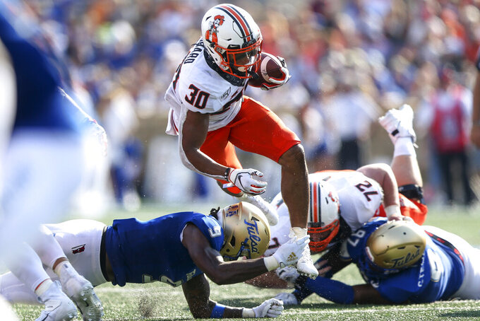 Oklahoma State running back Chuba Hubbard (30) jumps over Tulsa cornerback Reggie Robinson II (9) during an NCAA college football game Saturday, Sept. 14, 2019, in Tulsa, Okla. (Ian Maule/Tulsa World via AP)