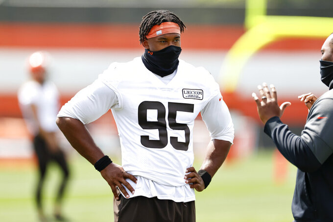 Cleveland Browns defensive end Myles Garrett (95) talks with a coach during practice at the NFL football team's training facility Friday, Aug. 14, 2020, in Berea, Ohio. (AP Photo/Ron Schwane)