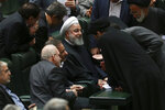 In this Monday, Feb. 4, 2019, photo, Iranian President Hassan Rouhani, center, listens to a lawmaker as he is surrounded by a group of lawmakers after defending his proposed health minister in an open session of parliament, in Tehran, Iran. Lashed by criticism over his collapsing nuclear deal, Iran's President Rouhani faces an uncertain future amid a renewed hard-line effort to drive him from office years before his elected term ends. Iranian presidents typically see their popularity erode during their second four-year terms. But analysts say Rouhani is particularly vulnerable because of the economic crisis assailing the country's rial currency, which has hurt ordinary Iranians and emboldened critics to call for his ouster.(AP Photo/Vahid Salemi)