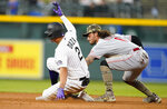 Colorado Rockies' Yonathan Daza, left, slides safely into second base with a double as Cincinnati Reds second baseman Jonathan India applies the tag in the fourth inning of a baseball game Friday, May 14, 2021, in Denver. (AP Photo/David Zalubowski)