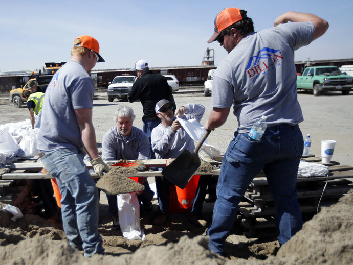 Volunteers fill sandbags in preparation for flooding along the Missouri River in St Joseph, Mo., Monday, March 18, 2019. Hundreds of homes flooded in several Midwestern states after rivers breached at least a dozen levees following heavy rain and snowmelt in the region, authorities said Monday while warning that the flooding was expected to linger. (AP Photo/Orlin Wagner)