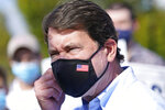 Bill Hagerty, the Republican nominee for U.S. Senate from Tennessee, removes his mask as he prepares to speak with reporters after voting during the early voting period Wednesday, Oct. 21, 2020, in Nashville, Tenn. (AP Photo/Mark Humphrey)