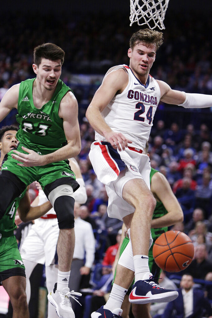 North Dakota forward Kienan Walter, left, and Gonzaga forward Corey Kispert go after the ball during the first half of an NCAA college basketball game in Spokane, Wash., Tuesday, Nov. 12, 2019. (AP Photo/Young Kwak)