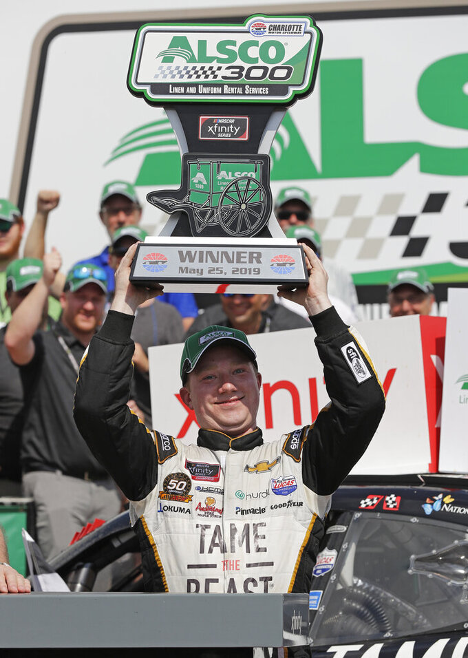 Tyler Reddick raises the trophy in Victory Lane after winning the NASCAR Xfinity Series auto race at Charlotte Motor Speedway in Concord, N.C., Saturday, May 25, 2019. (AP Photo/Chuck Burton)