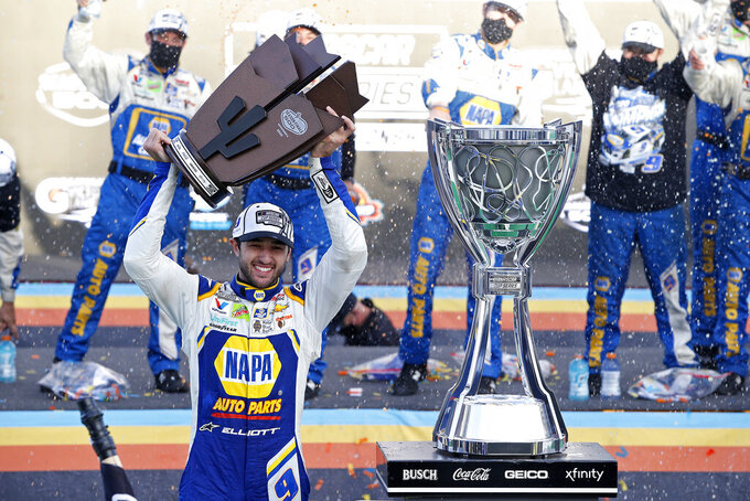 Chase Elliott holds up the race trophy in Victory Lane as celebrates his season championship after winning the NASCAR Cup Series auto race at Phoenix Raceway, Sunday, Nov. 8, 2020, in Avondale, Ariz. (AP Photo/Ralph Freso)
