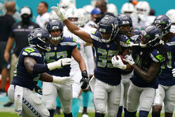 Seattle Seahawks cornerback Ryan Neal (35) is celebrated by his teammates after intercepting a pass, during the first half of an NFL football game against the Miami Dolphins, Sunday, Oct. 4, 2020 in Miami Gardens, Fla. (AP Photo/Wilfredo Lee)