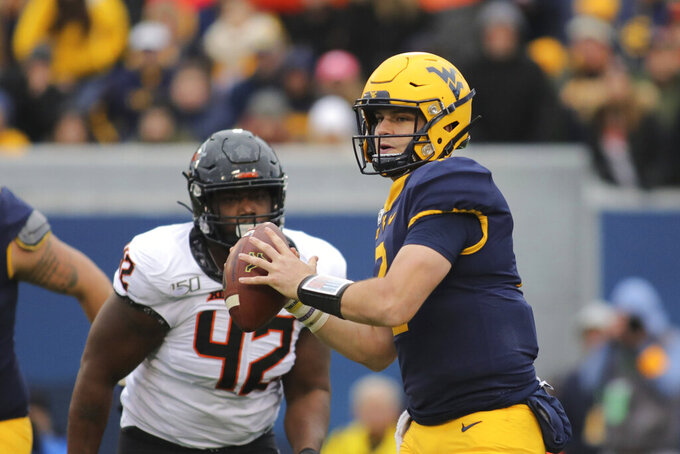 West Virginia quarterback Jarrett Doege (2) rolls out of the pocket as Oklahoma State's Jayden Jennings (42) pursues during the second quarter of their NCAA college football game  in Morgantown, W.Va., on Saturday, Nov. 23, 2019. (AP Photo/Chris Jackson)