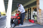 FILE - In this Wednesday, Oct. 9, 2019 file photo, Cliff Dunn, owner of Pawsarotti's pet store, runs a generator in order to keep a freezer full of raw pet food cold during a power outage in Santa Rosa, Calif. Power shutdowns intended to prevent more devastating California wildfires are raising concerns about another environmental threat: air pollution. As utilities temporarily halted service to more than 2 million people this week, many fired up standby generators that spew toxic emissions. (Christopher Chung/The Press Democrat via AP, File)