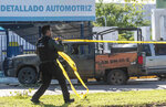A Mexican police officer deploys tape to secure the scene around a bullet riddled armed forces truck, a day after gunmen and members of Mexico security forces clashed in a large gun battle in Culiacan, Mexico, Friday Oct. 18, 2019. Mexican security forces backed off an attempt to capture a son of imprisoned drug lord Joaquin