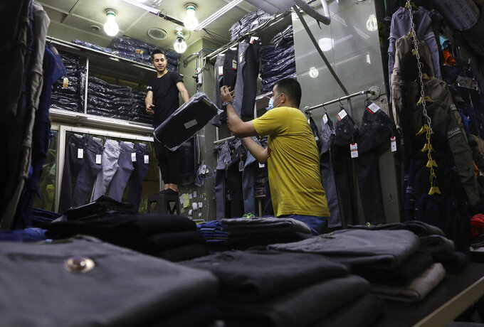 Shopkeepers stock new merchandise at the Grand Bazaar, in Tehran, Iran, Thursday, June 3, 2021. Iran's ailing economy is the major concern for those living in the Islamic Republic ahead of the country's presidential election. They face a daily grinding nightmare of high inflation, an ever-weakening national currency and high unemployment exacerbated by the coronavirus pandemic. (AP Photo/Vahid Salemi)