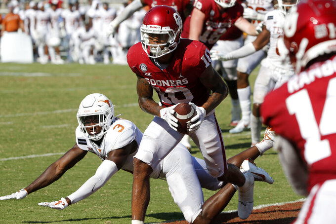 Oklahoma wide receiver Theo Wease (10) catches a two-point conversion as Texas defensive back Jalen Green (3) defends during the second half of an NCAA college football game in Dallas,Tx, Saturday, Oct. 10, 2020. Oklahoma defeated Texas 53-45 in four overtimes. (AP Photo/Michael Ainsworth)