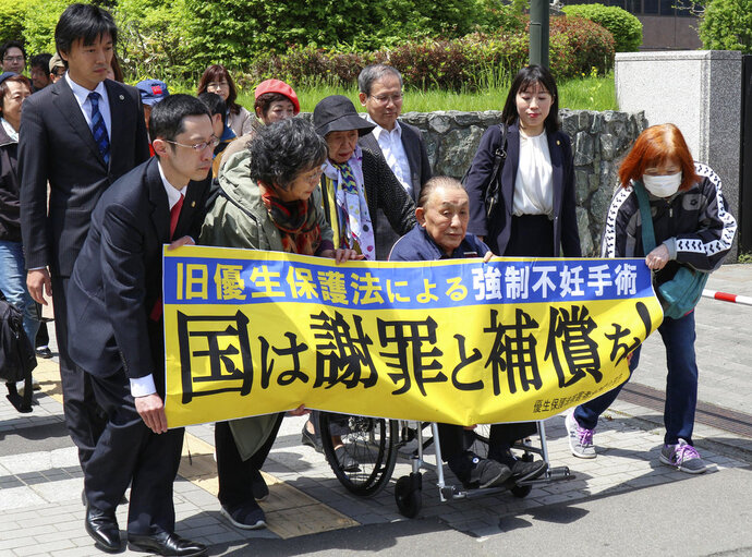 Kikuo Kojima, front third from left, a plaintiff who filed lawsuit against the government heads to the Sapporo district court in Sapporo, northern Japan Thursday, May 17, 2018. Three Japanese who were forcibly sterilized under a government policy decades ago have filed lawsuits demanding apology and compensation, in a movement growing across the country. The banner in Japanese reads