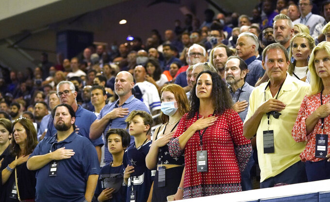 Dallas Cowboys fans stand for the national anthem before an NFL football practice in Frisco, Texas, Monday, Aug. 16, 2021. (AP Photo/LM Otero)