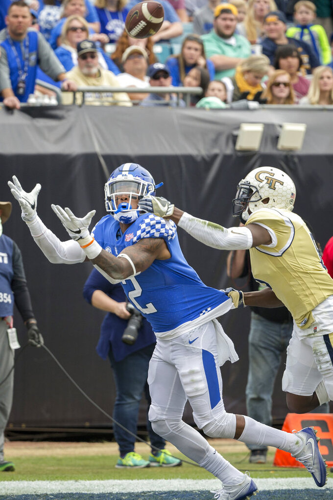 FILE - In this Dec. 31, 2016, file photo, Kentucky wide receiver Dorian Baker (2) catches a touchdown pass while being defended by Georgia Tech defensive back Step Durham (8) during the second half of the TaxSlayer Bowl NCAA college football game, in Jacksonville, Fla. Overcoming injuries that made walking difficult for Dorian Baker might explain why the Kentucky receiver is so eager to run back on the field. He has recovered from a season-ending ankle injury last August and is out to prove he can be a reliable target for the Wildcats.  (AP Photo/Stephen B. Morton, File)