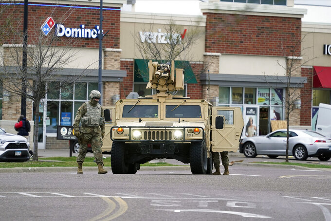 A National Guard soldier maintain watch and directs traffic at a shopping center in Brooklyn Center, Minn., a suburb of Minneapolis, Monday, April 12, 2021. A Black man died after being shot by police in a Minneapolis suburb during a traffic stop and crashing his car several blocks away, sparking violent protests that lasted into the early hours Monday as officers in riot gear clashed with demonstrators and the man's mother called for calm. (AP Photo/Jim Mone)