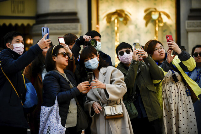People, some wearing sanitary masks, take photos in central Milan, Italy, Monday, Feb. 24, 2020. At least 190 people in Italy's north have tested positive for the COVID-19 virus and four people have died, including an 84-year-old man who died overnight in Bergamo, the Lombardy regional government reported. (Claudio Furlan/Lapresse via AP)