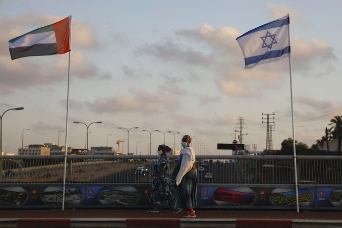 Women wearing face masks against the coronavirus walk past United Arab Emirates and Israeli flags at the Peace Bridge in Netanya, Israel, Sunday, Aug. 16, 2020. The UAE flag was displayed to celebrate last week's announcement that Israel and the United Arab Emirates have agreed to establish full diplomatic relations. (AP Photo/Ariel Schalit)