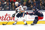 Edmonton Oilers' Alex Chiasson, left, looks for an open pass as Columbus Blue Jackets' Boone Jenner defends during the first period of an NHL hockey game Wednesday, Oct. 30, 2019, in Columbus, Ohio. (AP Photo/Jay LaPrete)